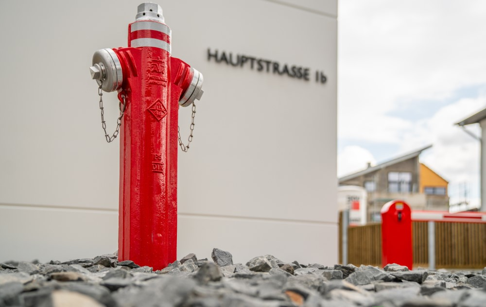 Das Bild zeigt einen roten Wasserhydranten