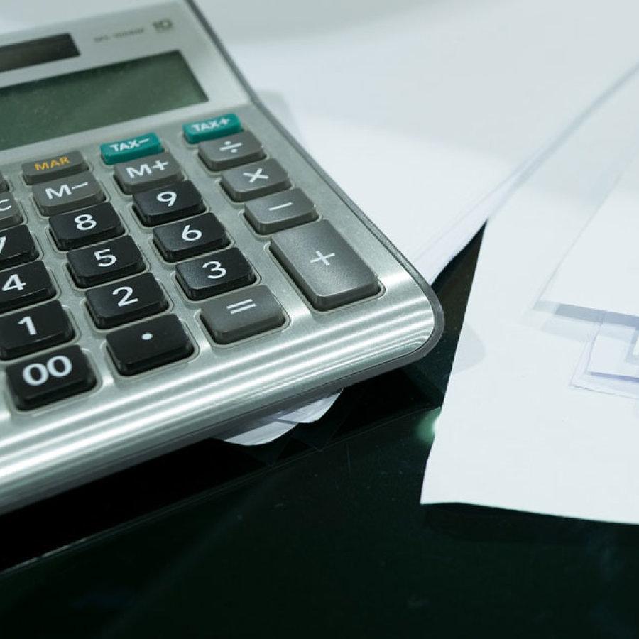 Das Bild zeigt einen Taschenrechner neben einem Stapel Unterlagen