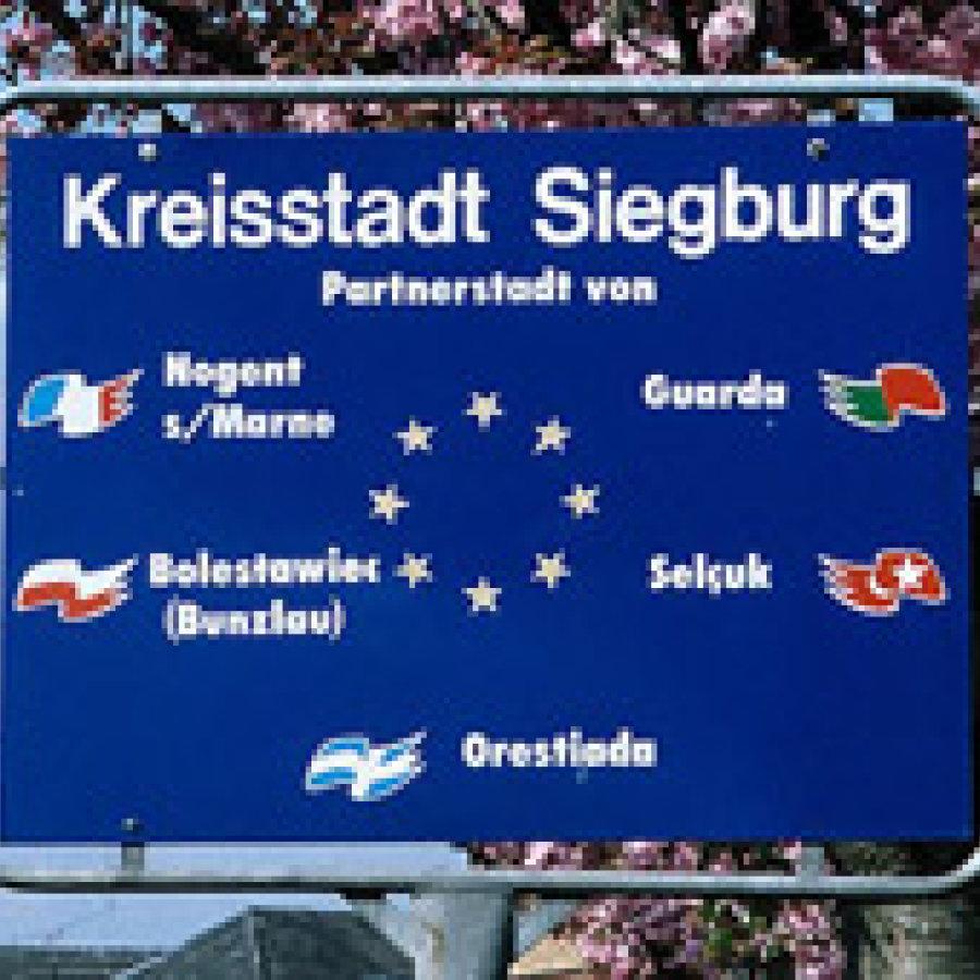 Das Bild zeigt eine blaue Informationstafel mit der Auflistung aller Partnerstädte von Siegburg