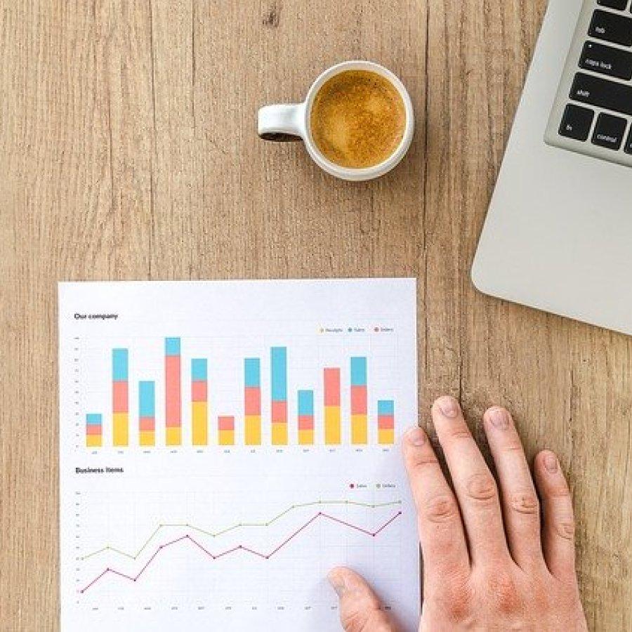 Das Bild zeigt ein Laptop, eine Tasse Kaffe sowie ein DIN A4 Blatt mit Statistiken auf einem Holztisch