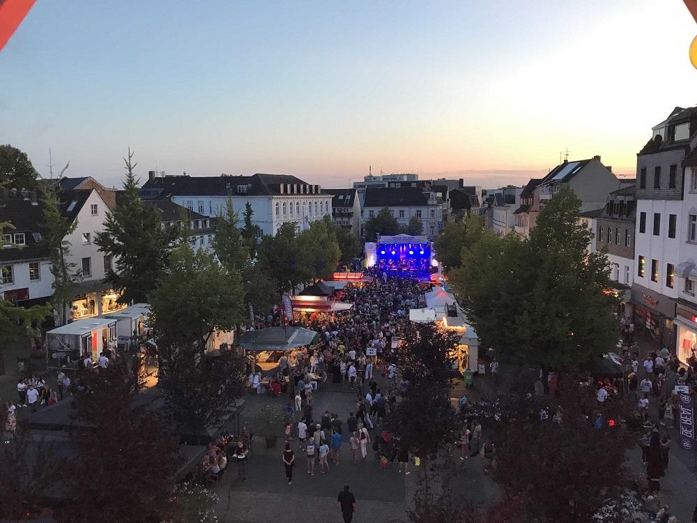 Luftbild von Menschen vor einer ausgeleuchteten Bühne auf dem Siegburger Markt, im Hintergrund Abendhimmel