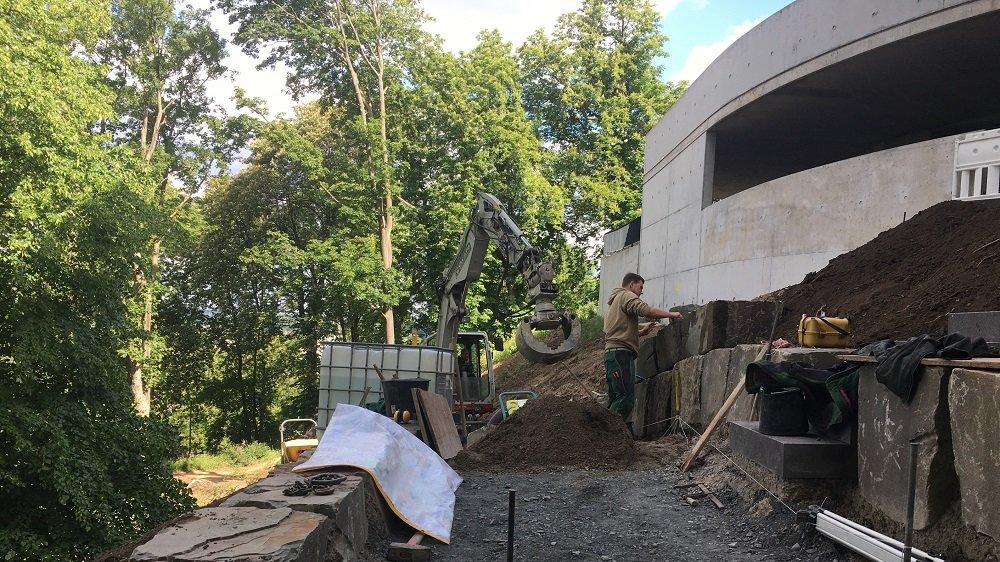 Bauarbeiter und Bagger zwischen großen Felsblöcken, die einen geschotterten Weg einrahmen