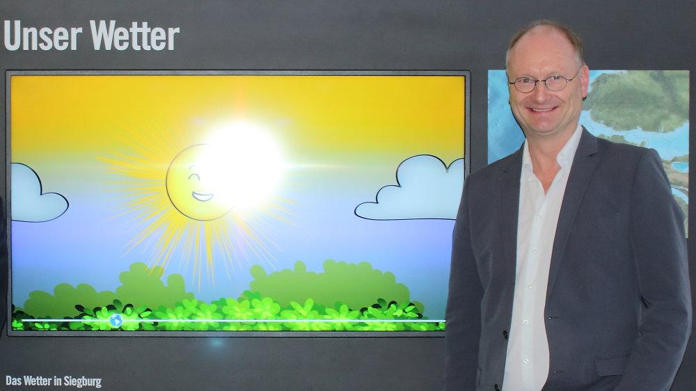 Ein Mann, Sven Plöger, steht neben einem Bild mit einer animierten Sonne