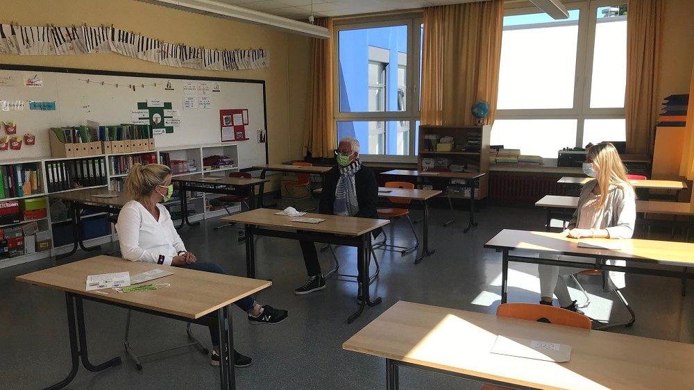 Bürgermeister Franz Huhn und Lehrerinnen mit Mundschutz an Schultischen
