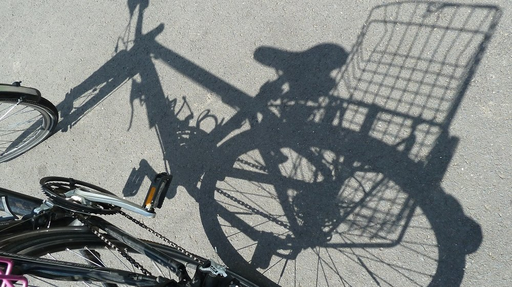 Schatten eines Fahrrads mit Korb auf dem Gepäckträger