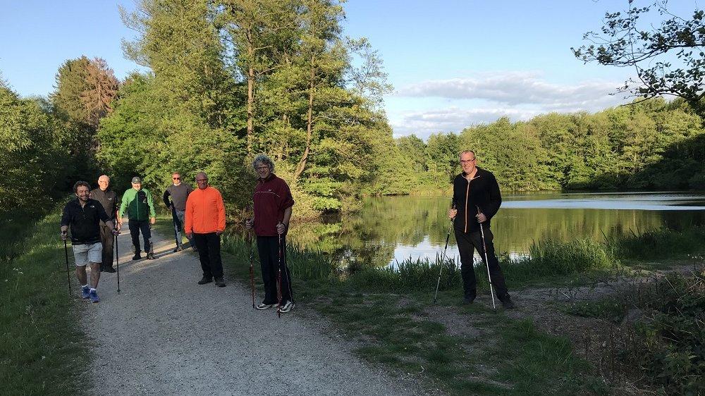 Sieben Männer mit Walkingstöcken stehen auf einem Waldweg neben einem Teich.