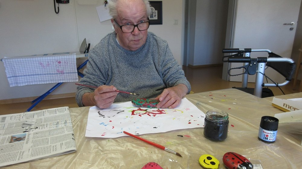 Älterer Mann bemalt einen Stein, vor ihm liegen weitere bereits bunt bemalte Steine