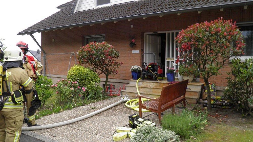 Feuerwehrleute vor einem Haus, in dessen Öffnung ein Entraucher steht