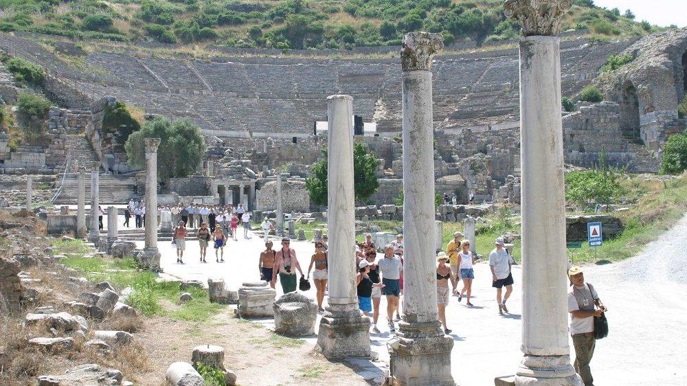 Besuchergruppe zwischen den Ruinen einer historischen Stadt.