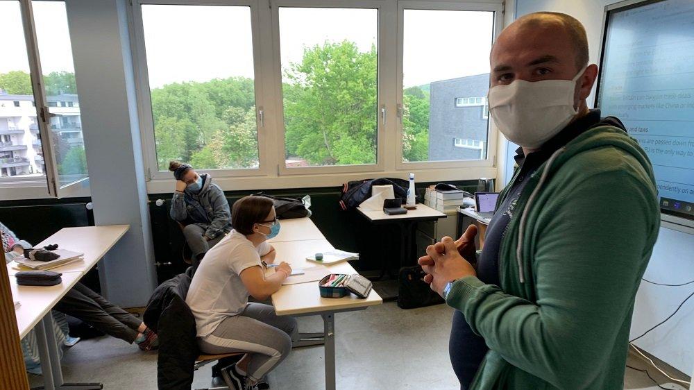 Lehrer und Schüler mit Mundschutz im Klassenraum
