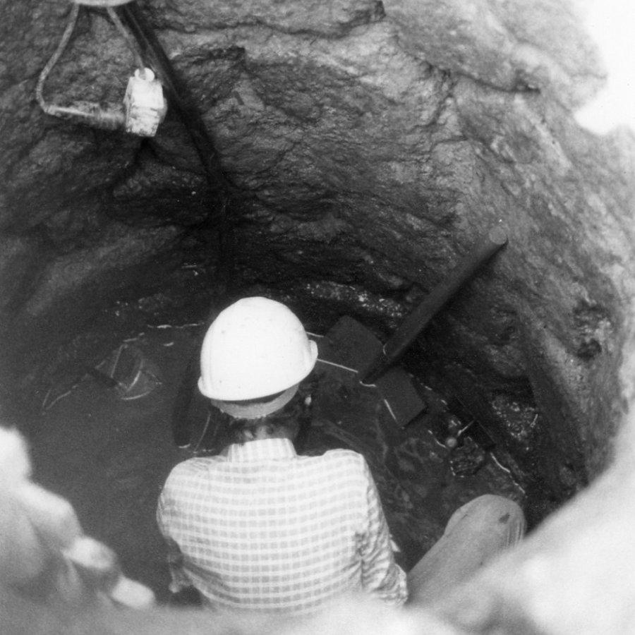 Archäologe in einem Grabungsloch