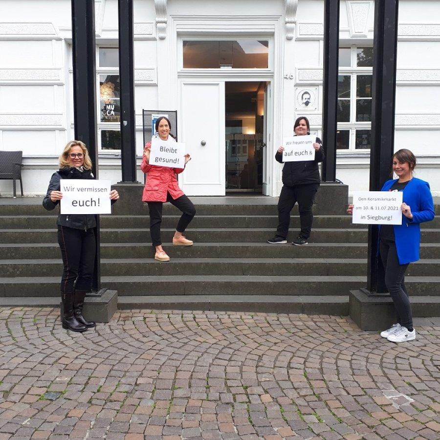 """Vier Frauen stehen auf einer Treppe und halten Schilder hoch: """"Wir vermissen euch! Bleibt gesund! Wir freuen uns auf euch & den Keramikmarkt am 10. & 11.07.2021 in Siegburg!"""""""