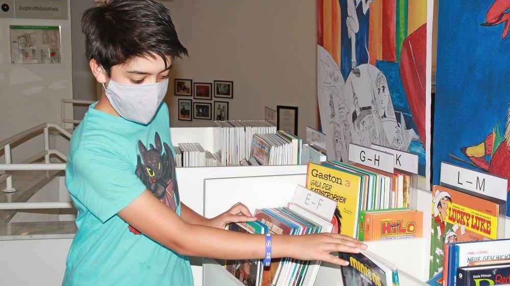 Junge mit Mundschutz blättert durch Comics in einem Regal