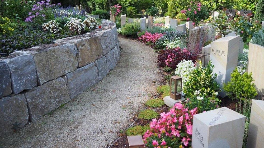 Grabsteine neben einer runden Mauer.