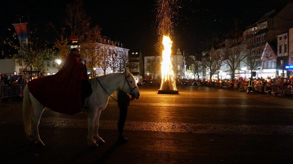 St. Martin auf einem weißen Pferd vor dem Martinsfeuer auf dem markt, rundherum dicht gedrängte Kindergruppen.