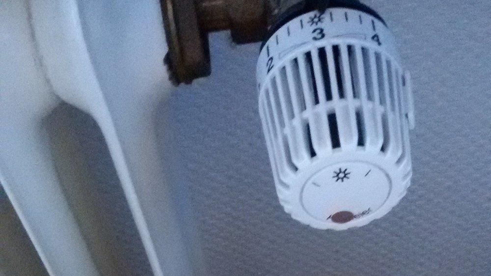 Thermometer vor Heizung mit Thermostat auf Stufe 3