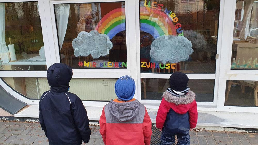 Drei Kita-Kinder vor dem Fensterbild der Kita Deichmäuse