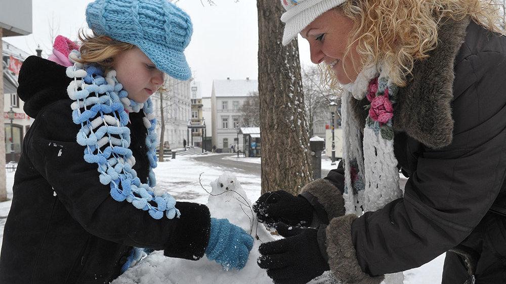 Mutter und Tochter bauen kleinen Schneemann