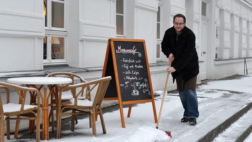 Harry Goltz beim Schneeschieben auf den Stufen vor dem Stadtmuseum