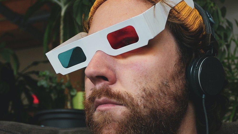 Mann mit Mütze, 3-D-Brille und Kopfhörern