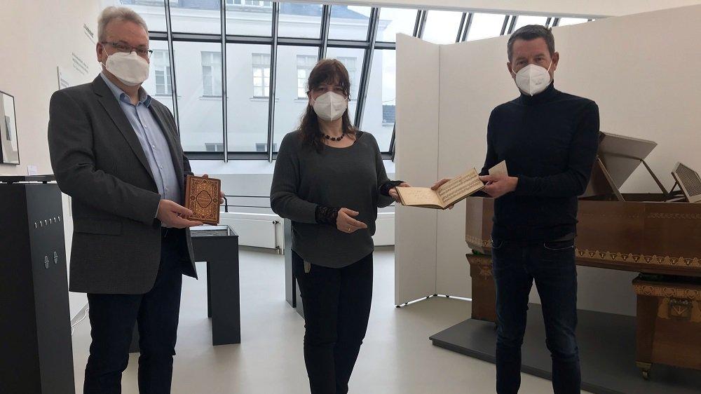 Kai Diekmann übergibt das Poesiealbum an Museumsleiterin Dr. Gundula Caspary. Dr. Christian Ubber hält den Gedichtband des Humperdinckvaters Gustav in Händen.