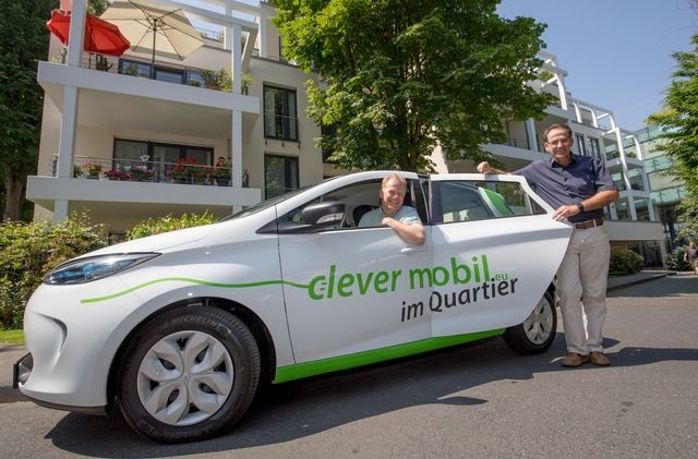 Thomas Zwingmann im und Thomas Schmitz an einem E-Auto