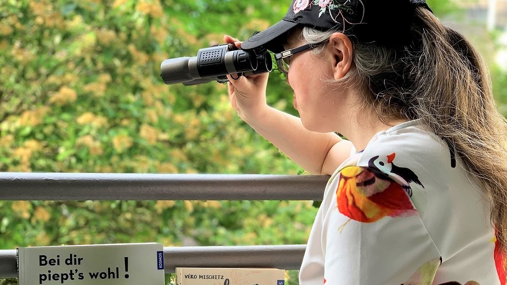 Frau mit Fernglas blickt ins Grüne, vor ihr stehen verschiedene Vogelkunde-Bücher