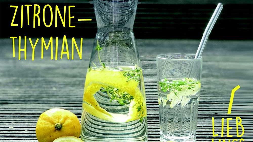 Eine Glasflasche, ein Glas mit Wasser und Zitronenschale