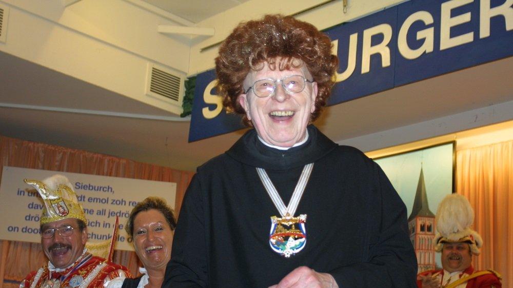 Pater Mauritius auf der Karnevalsbühne und der Perücke von Marita Köllner (links neben ihm) auf dem Kopf