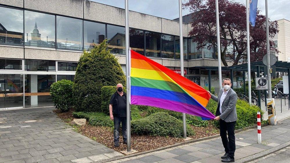 """Bürgermeister Stefan Rosemann und Hausmeister Anton """"Toni"""" Bäcker hissen die Regenbogenflagge am Rathaus."""