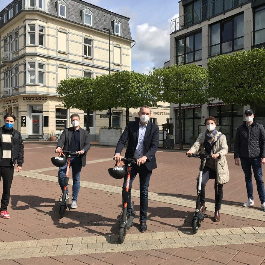 Ordnungsamtleiter Thomas Dammig, Bürgermeister Stefan Rosemann sowie die Technische Beigeordnete Barbara Guckelsberger auf E-Scootern, flankiert von Vertretern der Anbieter, Louis Andreae, Spin, links, und Sebastian Apfel, Bird.