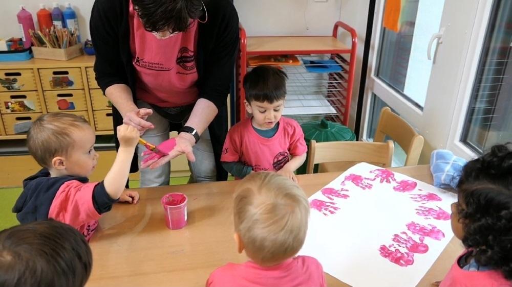 Kleinkinder in pinken T-Shirts am Basteltisch