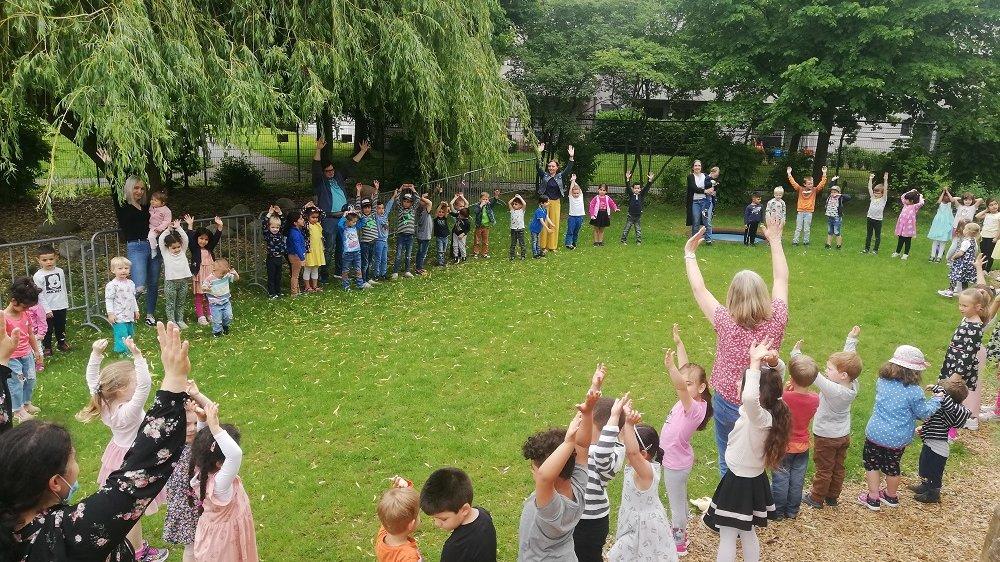 Kindergruppe steht im Kreis im Garten