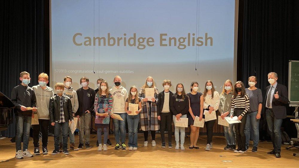 """Siebtklässler des Anno-Gymnasiums, eine Lehrerin und Schulleiter Sebastian Kaas vor dem Schriftzug """"Cambridge English"""""""