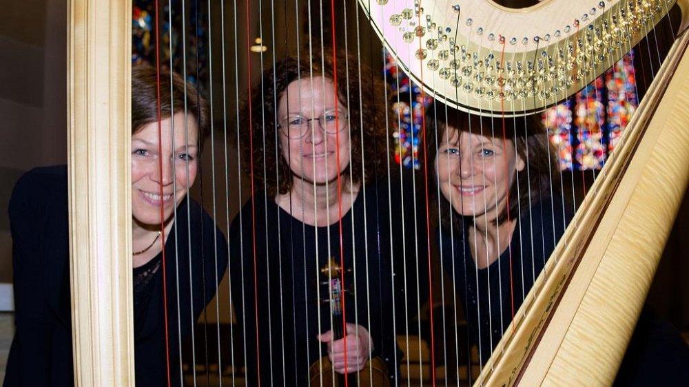 Karen Fälker-Herkenhöhner, Bettina Hanschel- Lüdemann und Agnieszka Gralak hinter den Saiten einer Harfe